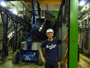 Me showing off the required underground fashion accessory (hard hat) and capturing a moment of our detector in construction.  The cherry picker is used to hoist the crew above the detector to install the electronics (the blue cylinders sticking out of the top).