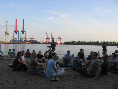 Members of the CALICE AHCAL group at a beach on the banks of the river Elbe in Hamburg. You can see the container terminal of Hamburg harbor in the distance.