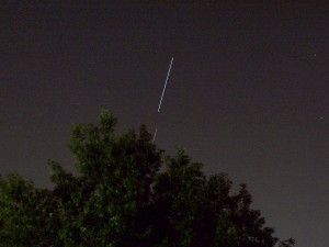 Discovery and ISS setting behind a tree.