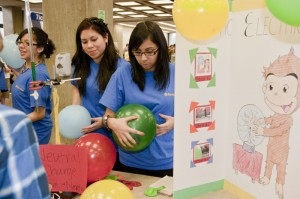 Students from Cristo Rey Jesuit High School in Chicago use ballons and Curious George to demonstrate static electricity. Credit: Fermilab/Cindy Arnold