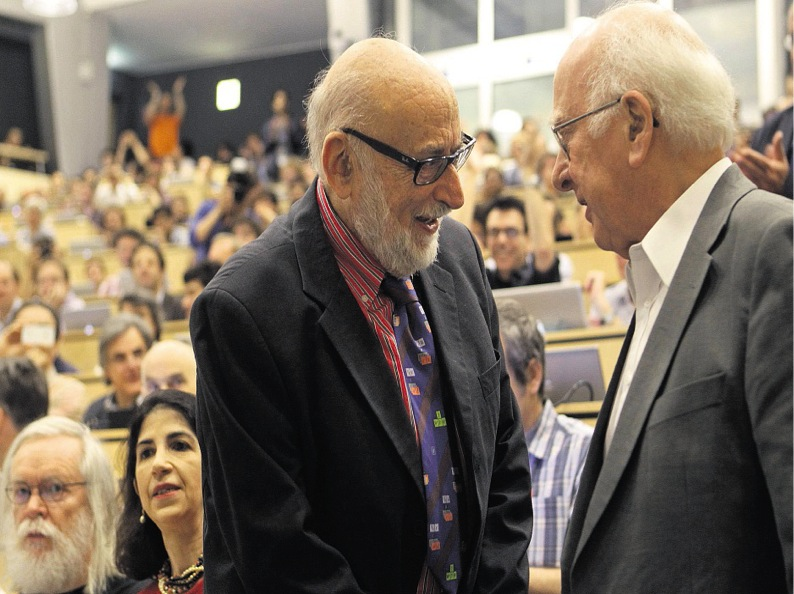 Peter meet François - Professors Higgs and Englert, who collaborated during the 1960s, meet for the first time on 4 July 2012. Notice the back of the room is filled with last years summer students who camped overnight for seats for the Higgs announcement.