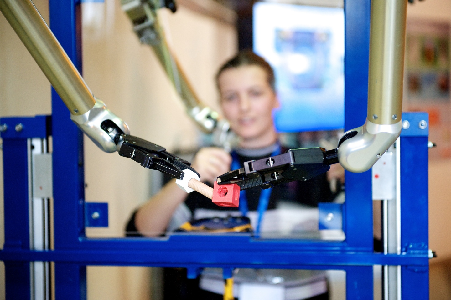 Visitor playing with robotic machine in metrology lab.
