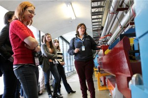 Fermilab docent Toni Mueller shows students a model of a beamline. The Midwest Conference for Undergraduate Women in Physics coordinators offered participants a tour of Fermilab or Argonne. Photo: Amanda Solliday