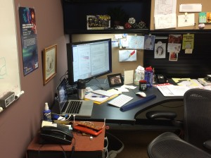 The main thesis editing desk: laptop, external monitor keyboard mouse; coffee, water; notes; and lots of encouragement.