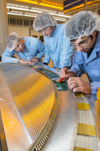 From left: Jason Bono (Rice University), Dan Ambrose (University of Minnesota) and Richie Bonventre (Lawrence Berkeley National Laboratory) work on the Mu2e straw chamber tracker unit at Lab 3. Photo: Reidar Hahn